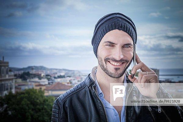 Porträt eines Mannes auf dem Dach  der auf Smartphones spricht  Cagliari  Sardinien  Italien
