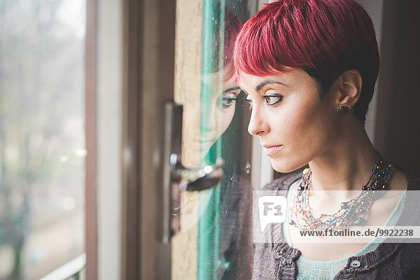 Young woman looking out of window  pensive expression