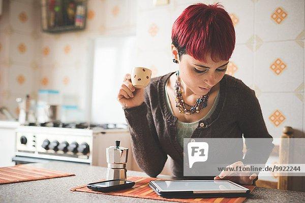Junge Frau  die am Tisch sitzt und Kaffee trinkt  mit Hilfe eines digitalen Tabletts.