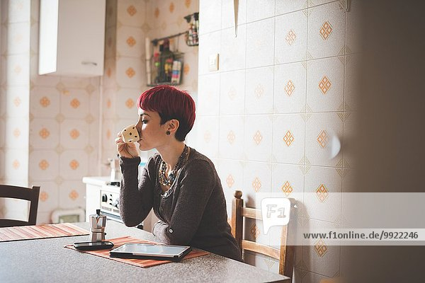 Junge Frau sitzt am Tisch und trinkt Kaffee.