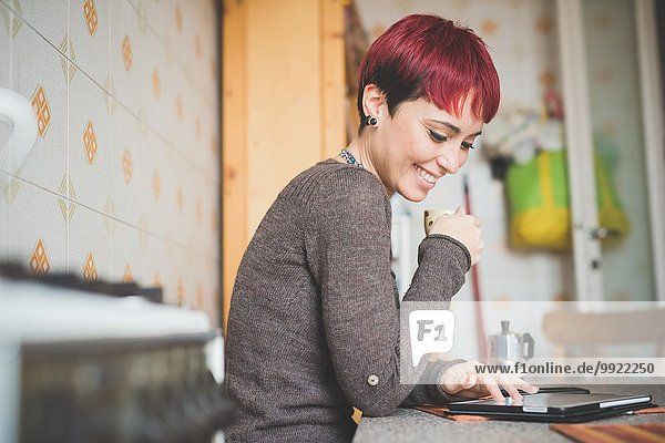 Junge Frau sitzt am Tisch  trinkt Kaffee und schaut auf die digitale Tafel.