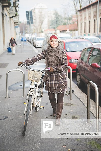 Porträt einer jungen Frau  die mit dem Fahrrad die Straße entlang läuft und Winterkleidung trägt.
