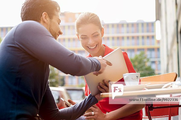 Junger Mann und junge Frau sitzen vor dem Café und schauen auf das digitale Tablett.