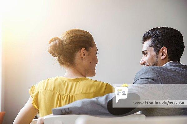 Junges Paar im Café sitzend  Rückansicht