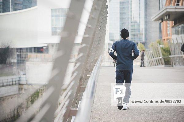Rückansicht des jungen Läufers auf der Stadtbrücke