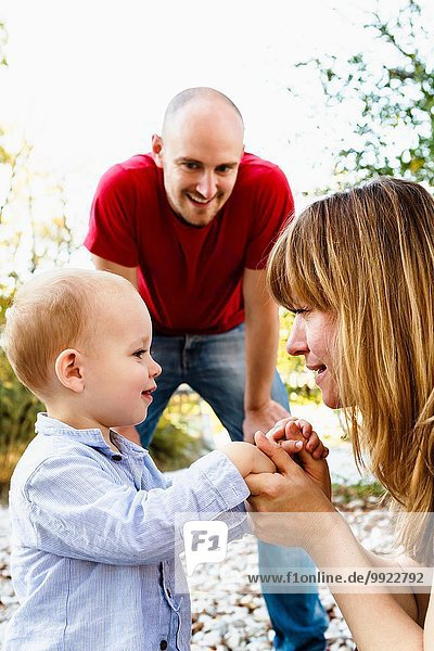 Sohn von Angesicht zu Angesicht mit Mutter  Händchen haltend  während Vater zusieht