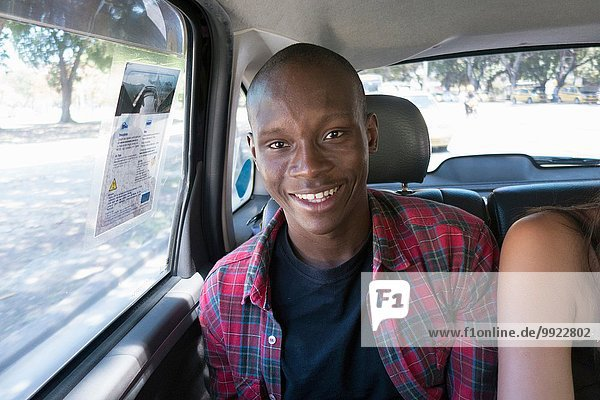 Junger Mann im Auto lächelnd  Portrait
