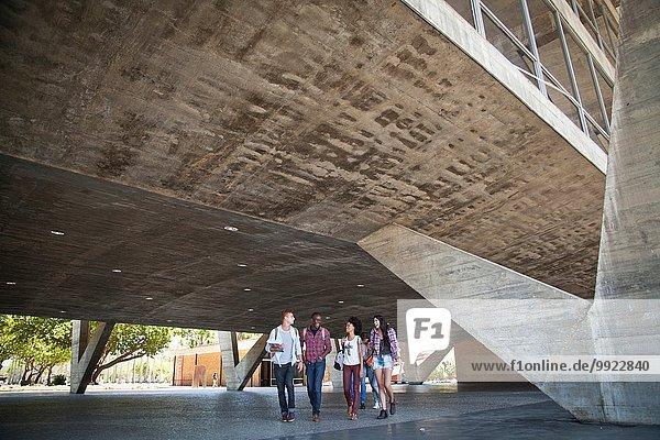 Vier Studenten  die unter dem Gebäude spazieren gehen.