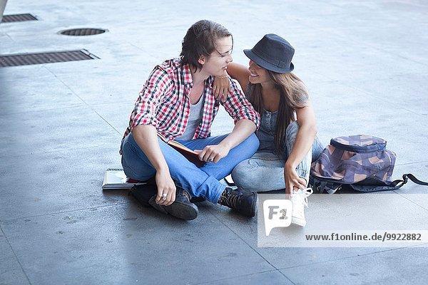 Junges Paar auf dem Boden sitzend
