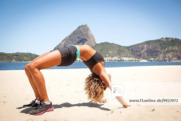 Junge Frau in Krabbenstellung am Strand  Rio de Janeiro  Brasilien