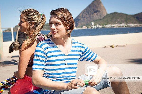 Junger Mann und Frau sitzen Rücken an Rücken  im Freien