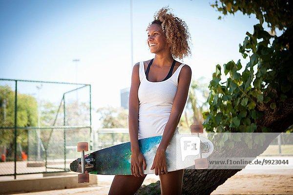 Porträt einer jungen Frau mit Skateboard
