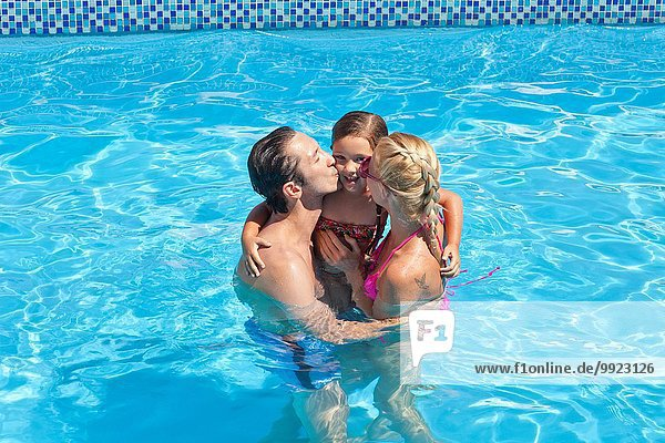Young family in pool together  mother and father kissing daughter on cheek