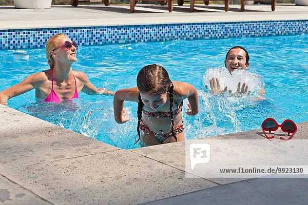 Young family fooling around in outdoor pool