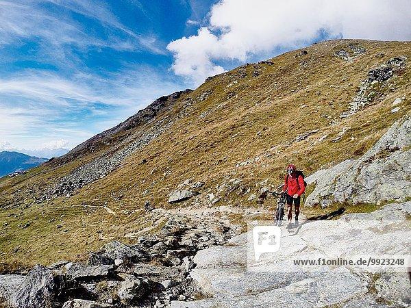 Mountainbiker schieben Fahrrad über Felsen  Wallis  Schweiz