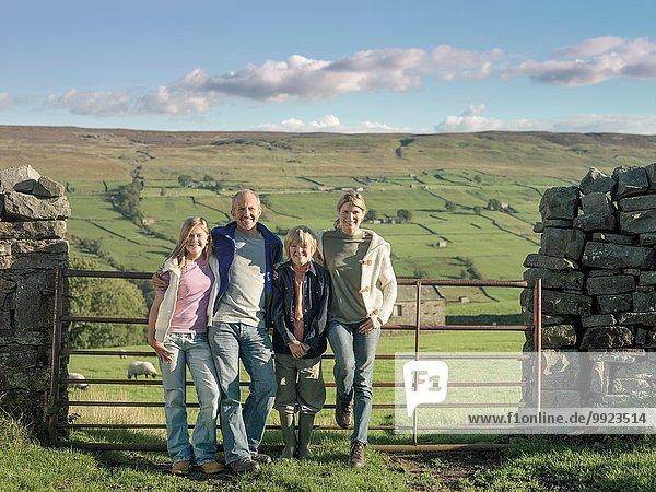 Porträt der Bauernfamilie vor dem Tor in ländlicher Landschaft