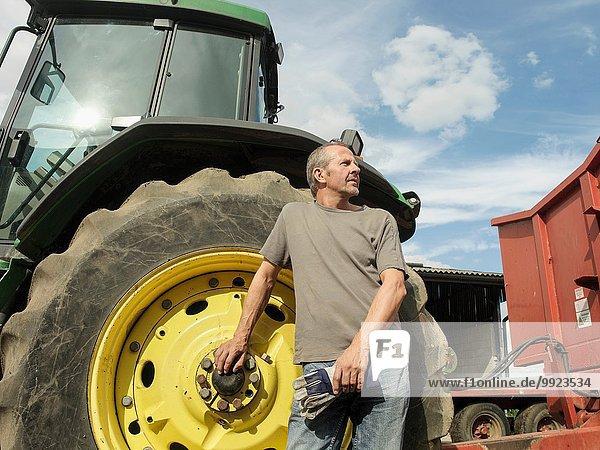 Porträt eines Landwirts  der neben dem Traktor steht und wegschaut.