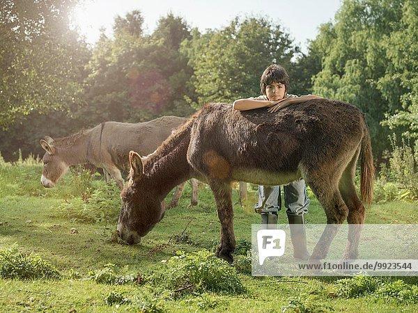 Boy with donkey in field  portrait