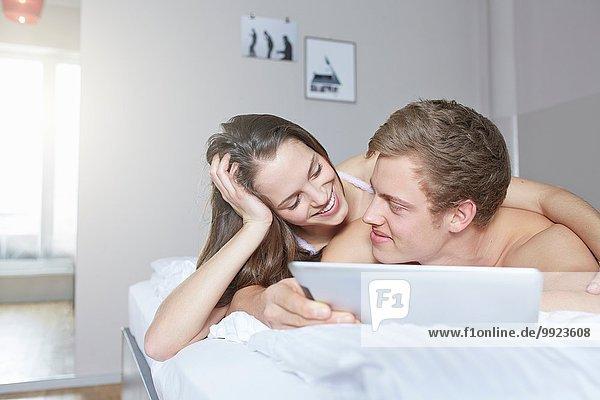 Junges Paar beim Durchblättern des digitalen Tabletts auf dem Bett