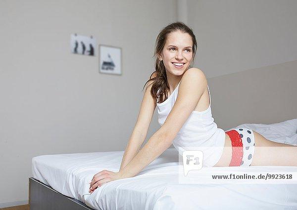 Porträt einer jungen Frau in Unterwäsche auf dem Bett