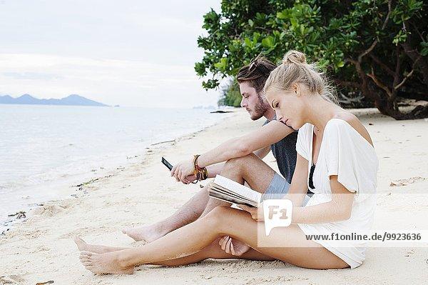 Junges Paar sitzt am Strand und liest Buch und SMS  Kradan  Thailand