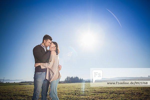 Junges Paar beim Küssen im Feld