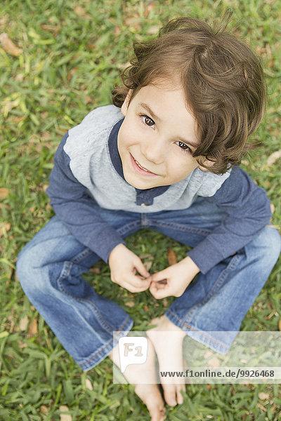 hoch oben sitzend sehen lächeln Junge - Person Gras hoch,oben,sitzend,sehen,lächeln,Junge - Person,Gras