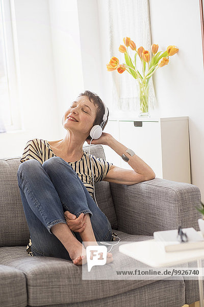 Smiling senior woman with headphones sitting on sofa