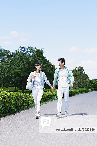 Happy Japanese couple in a park
