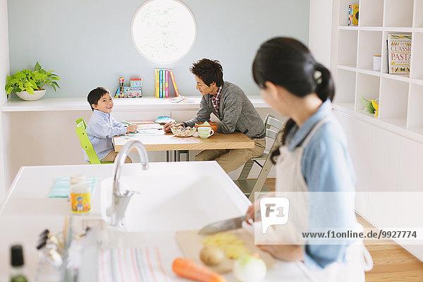 kochen sehen Menschlicher Vater Sohn am Tisch essen offen Küche Tisch Mutter - Mensch Hausaufgabe