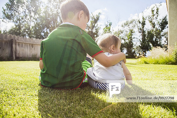 Brother (6-7) and sister (6-11months) sitting in grass