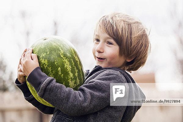 Boy (6-7) carrying watermelon