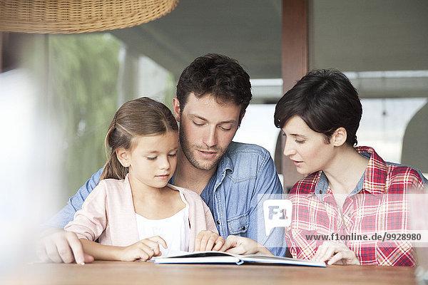 Kleines Mädchen beim Lesen mit ihren Eltern