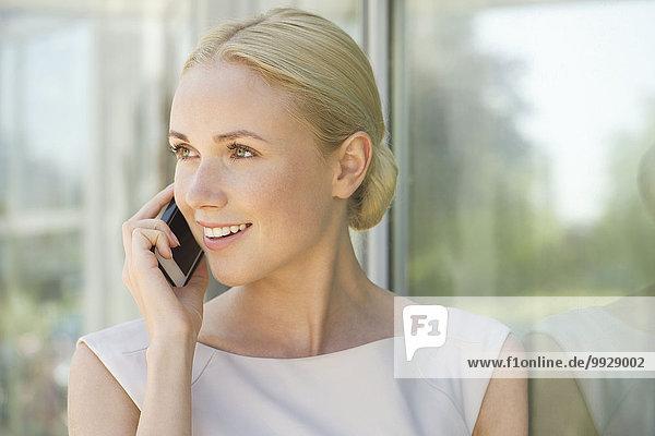 Frau spricht auf dem Smartphone  lächelnd