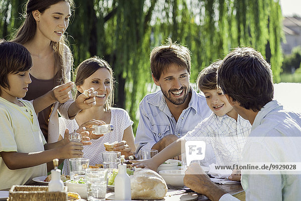 Familie beim gemeinsamen Frühstück im Freien
