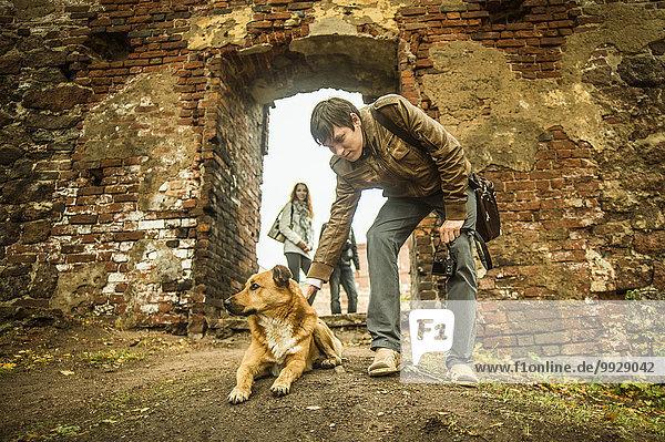 nahe Europäer Mann Hund Ruine streicheln