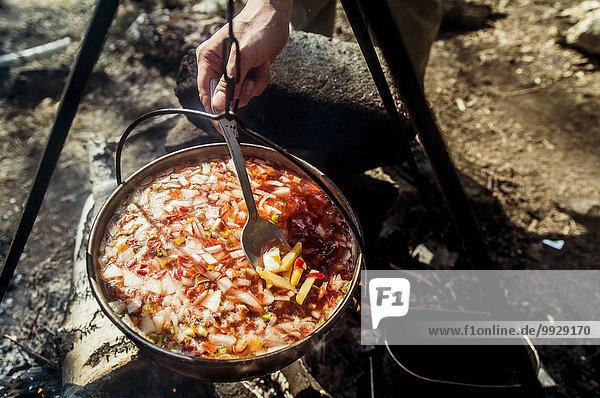 Lagerfeuer kochen über Mensch Close-up rühren Suppe