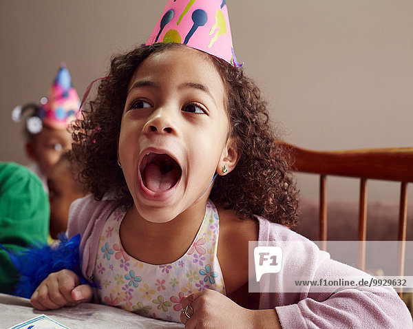 Shouting girl wearing party hat with mouth open