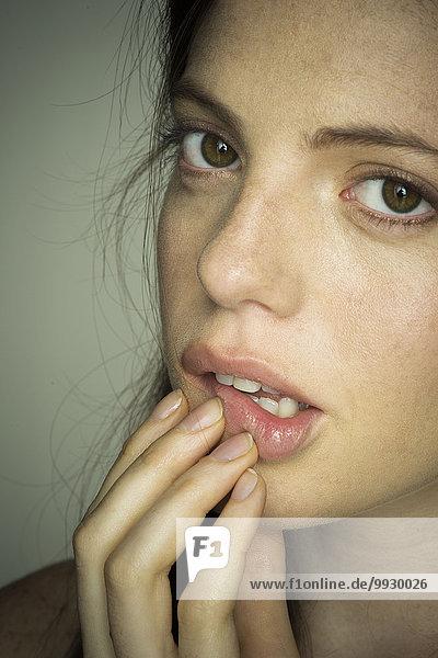 Junge Frau berührt nervös die Lippen  Porträt