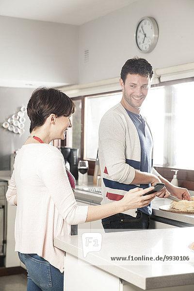 Paar  das zusammen auf das Smartphone schaut  während es Essen in der Küche zubereitet.