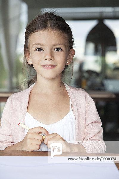 Kleines Mädchen sitzend mit Stift und Papier  Portrait
