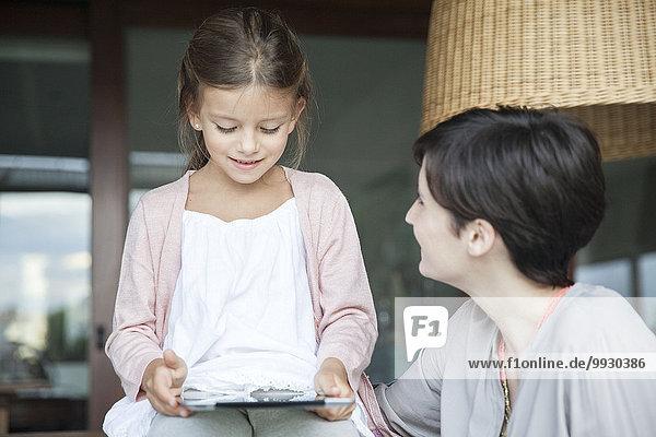 Mutter und kleine Tochter benutzen gemeinsam ein digitales Tablett.