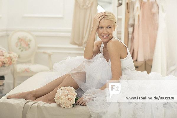 sitzend Blumenstrauß Strauß Braut lächeln Bett