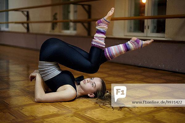 Caucasian dancer stretching back on studio floor