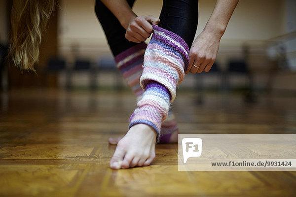 Caucasian dancer pulling on leg warmers