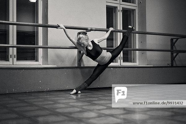 Caucasian dancer doing splits on barre in studio