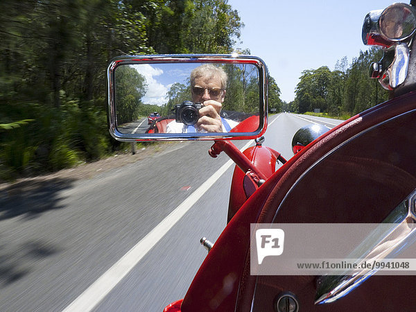 Pacific Highway  NSW  new south Wales  Australia  mudguard  trees  speed  blur  effect  MG  sports car  straight road  ahead  photographer  reflected  reflection  side mirror  red  motor  vehicle  perspective  white  line  vintage  old  classic  M G  camera  photo  photographing  silver  man