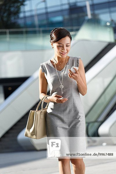 Young business woman looking at cell phone
