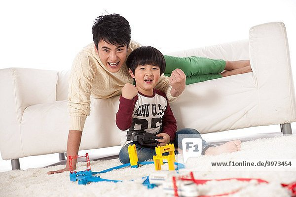 Father and son in the sitting room to play cars