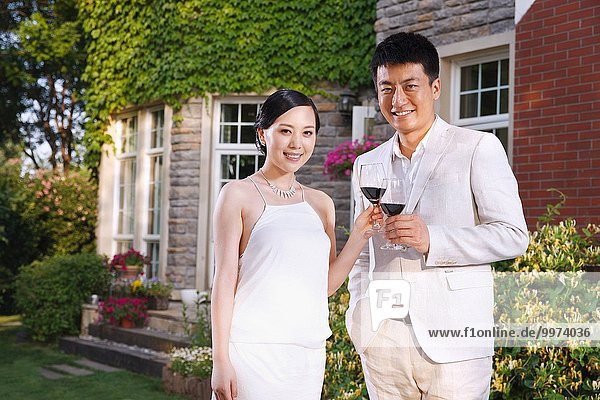 Romantic Oriental couples with wine in the garden